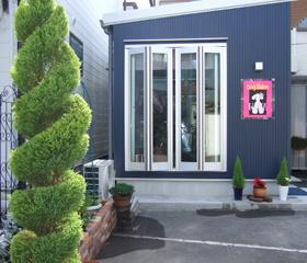 紺の外壁にピンクのロゴのコントラストが目立つ外観