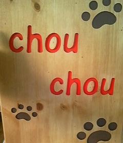 木に彫られたお店のロゴと犬の足跡