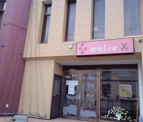 クリーム色の壁に薄いピンクの店看板