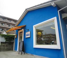 鮮やかな青い壁のお店外観